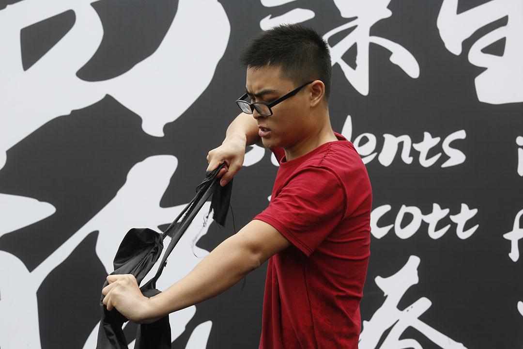 9月2日,中大百萬大道的罷課集會上,一名學生上台撕標語。