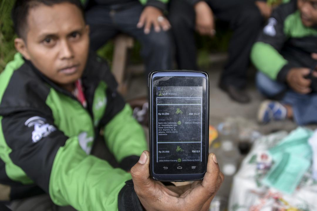 一位摩托車司機展示Gojek的應用程式。