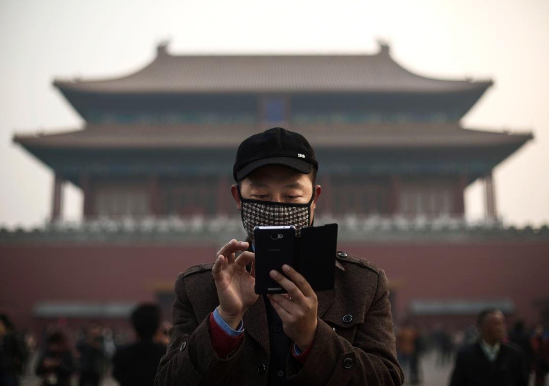 北京,一名正在使用手機的男子。 攝:Kevin Frayer/Getty Images