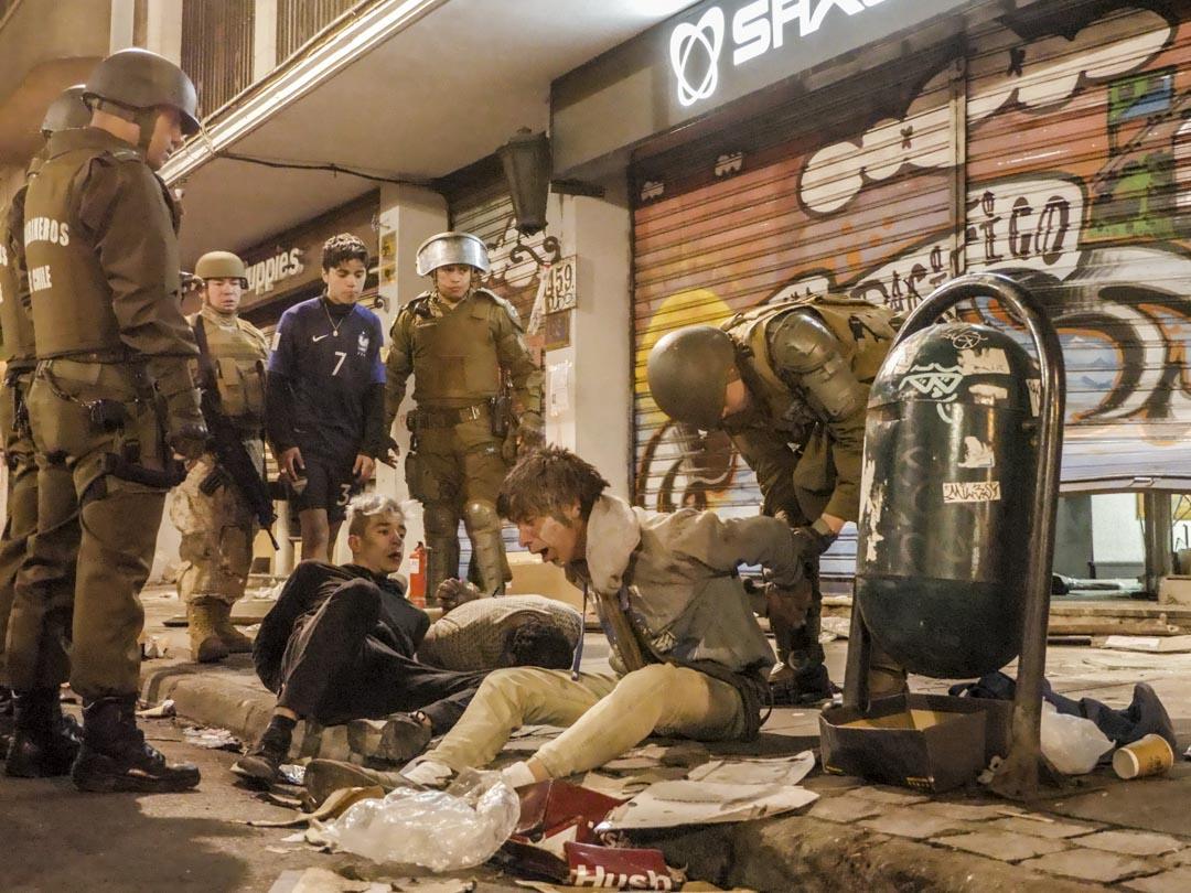 2019年10月25日晚,宵禁時分,軍警在智利城市瓦爾帕萊索(Valparaiso)街頭逮捕兩名抗議者。 攝影:Matthieu Le Mau