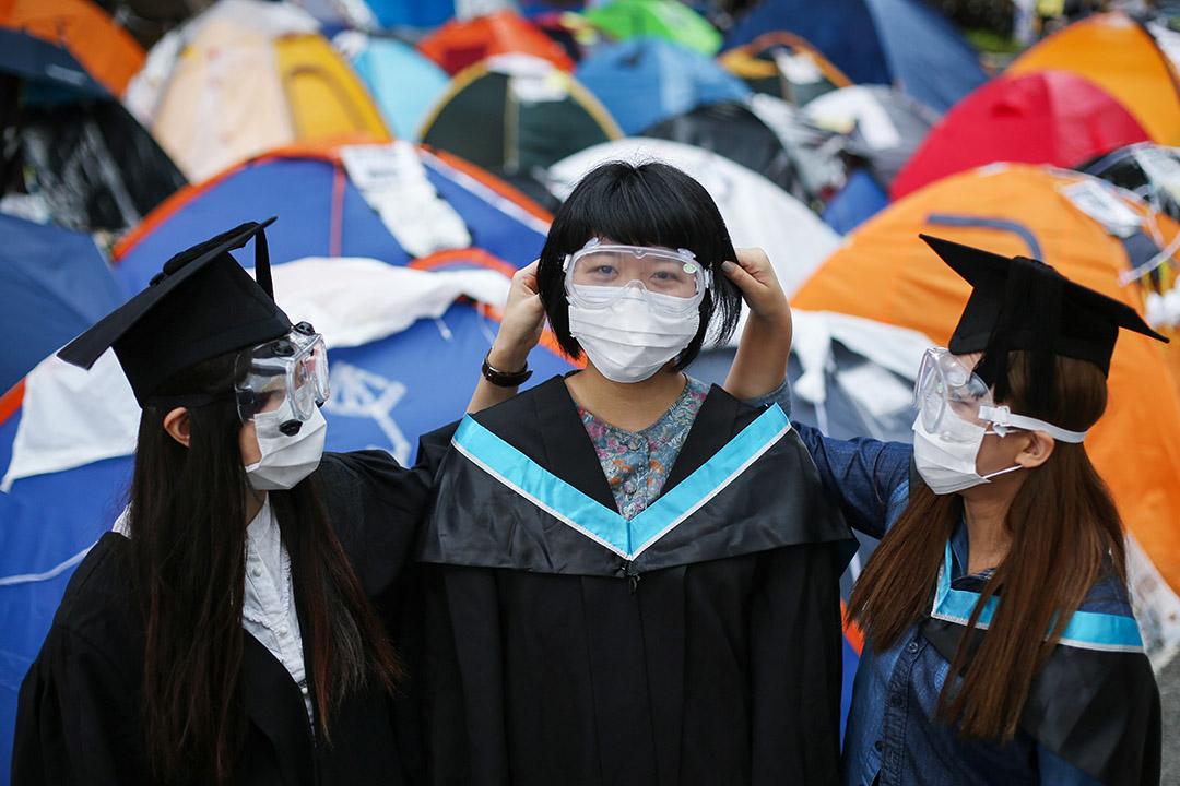 2014年10月25日,大學的畢業生於雨傘運動金鐘佔領區合影。
