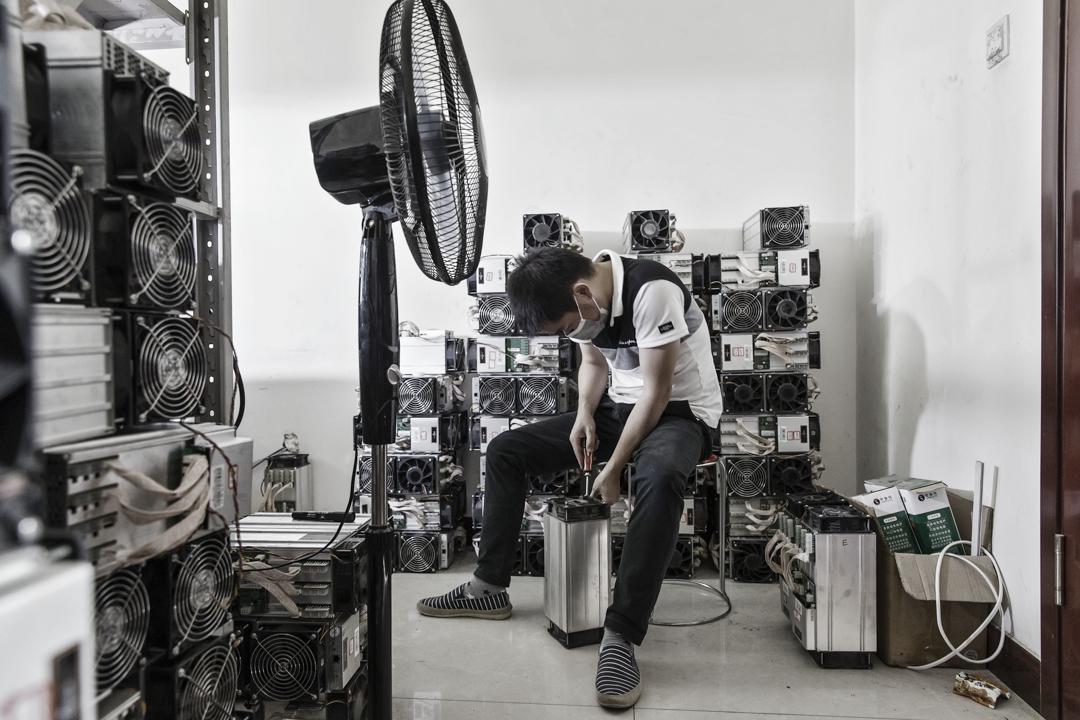 中國內蒙,一個技術人員正在維修比特幣「礦場」裡的電腦。 攝:Qilai Shen/Bloomberg via Getty Images