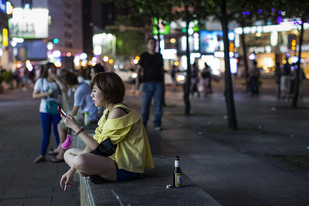 一名女子在台北的街頭看手機及抽煙。