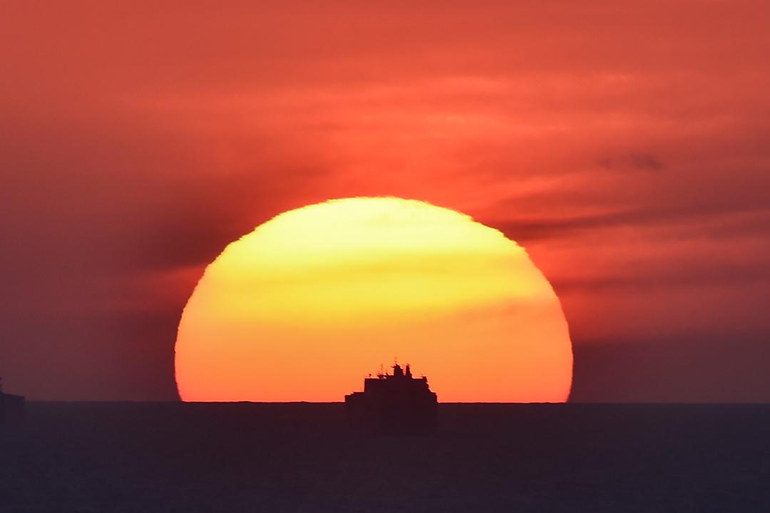 2019年5月9日,貨輪在日落時等待進入法國勒阿弗爾港口。 攝:Jean Francois Monier/AFP via Getty Images