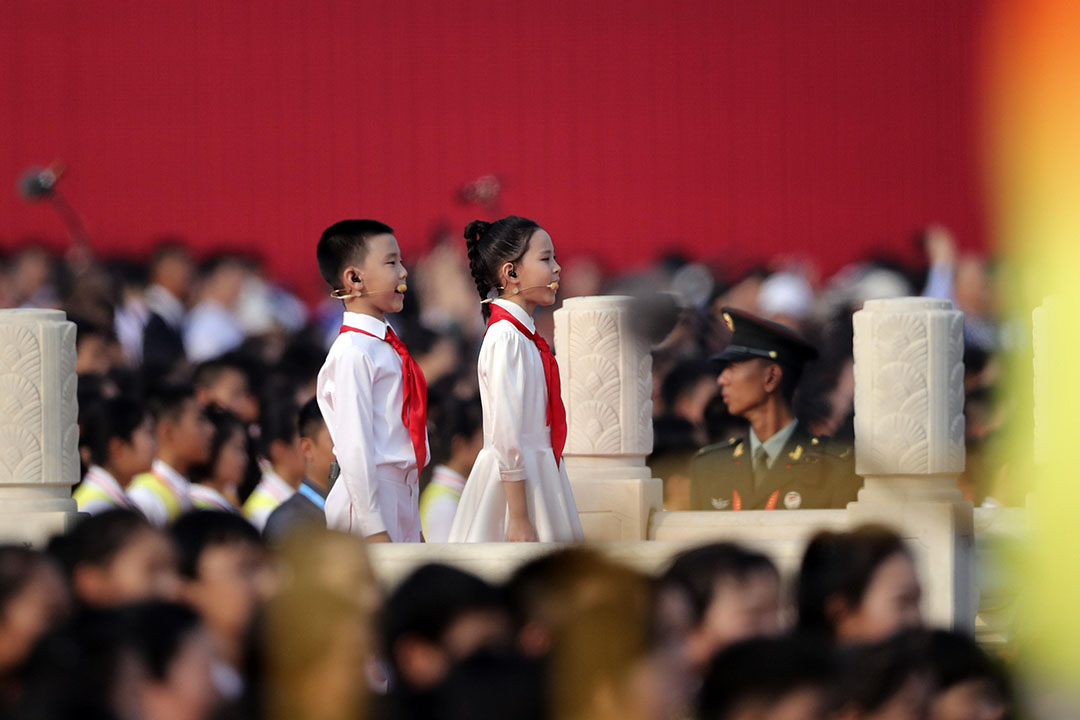 兩名戴着紅領巾的兒童在群眾遊行開始前唱歌。