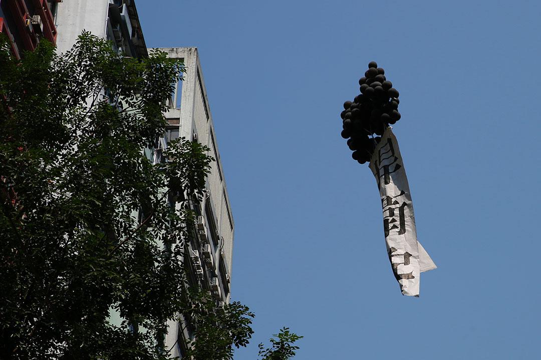 銅鑼灣有人放飛黑色氣球。