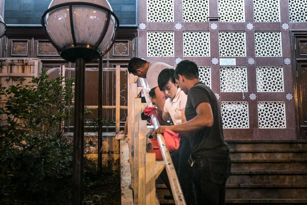 2019年10月20日,尖沙咀清真寺大門被水炮車射中,職員正在清潔欄杆。 攝:陳焯煇/端傳媒