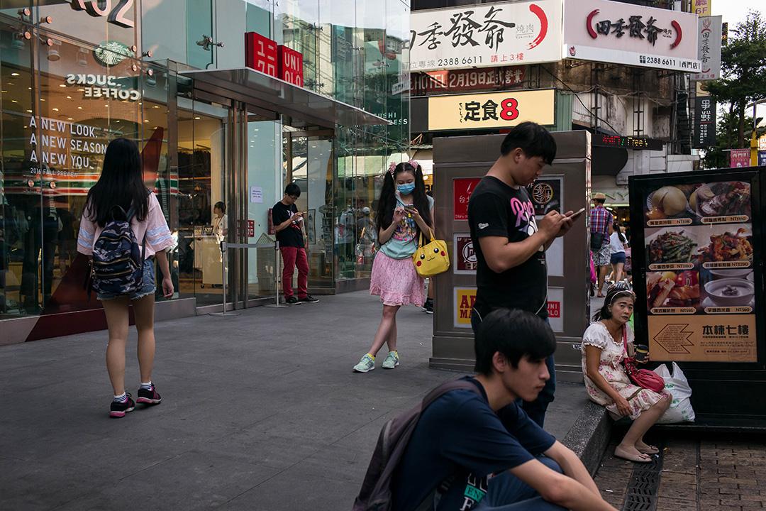2016年8月8日,人們在台北西門看他們的智能手機。