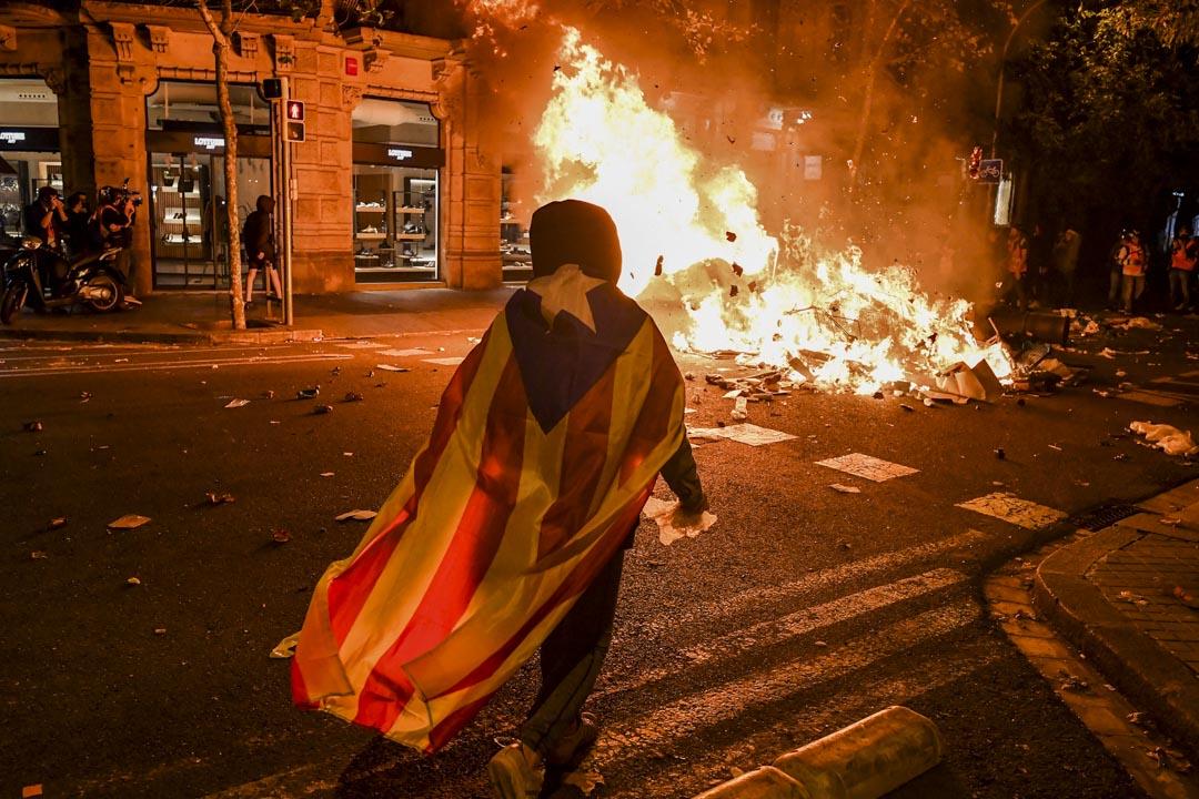2019年10月17日,巴塞羅拿示威持續,一名加泰羅尼亞示威者在一架焚燒中的車輛前。