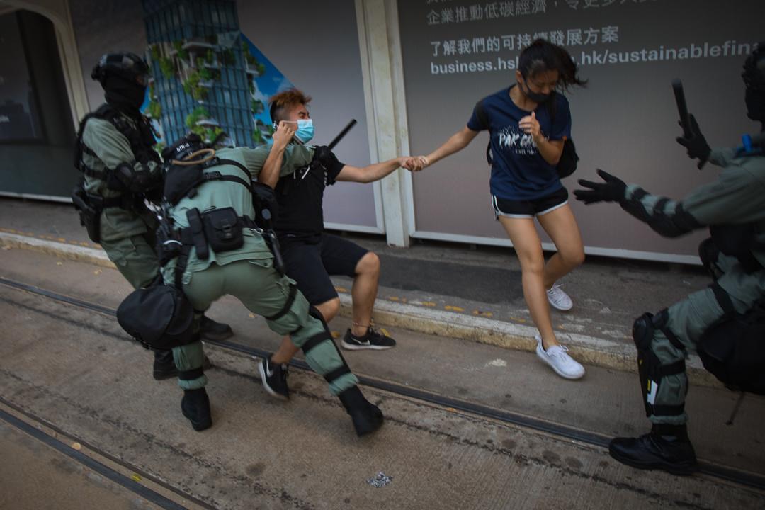 2019年10月5日,兩名戴著口罩的示威者被警察攻擊。 攝:陳焯煇/端傳媒