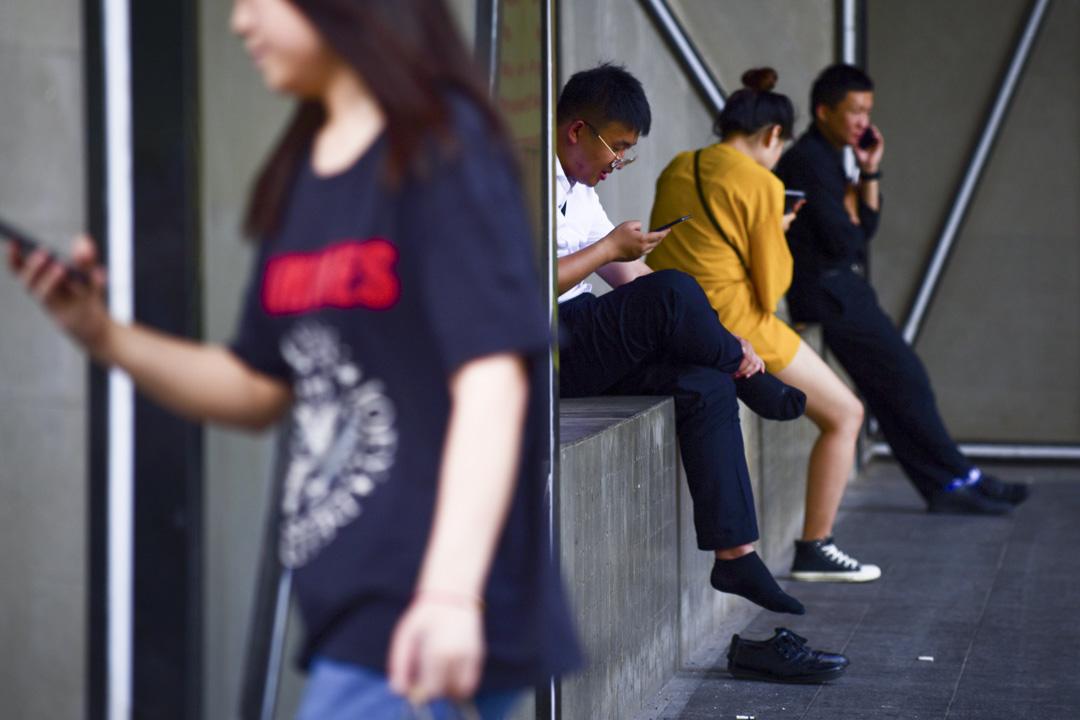 北京一個商場外,不少人都拿著電話觀看。 攝:Wang Zhao/AFP/Getty Images