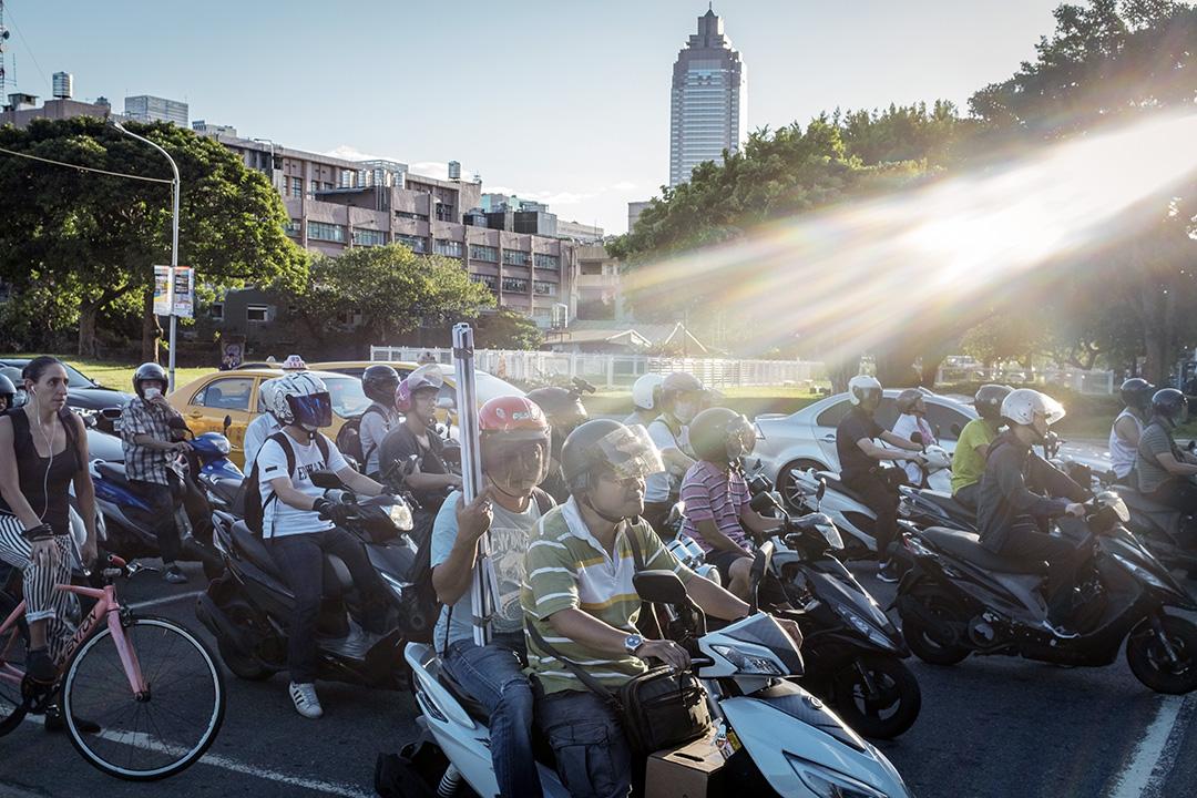 市民在台北騎著機車等待馬路。 攝:陳焯煇/端傳媒