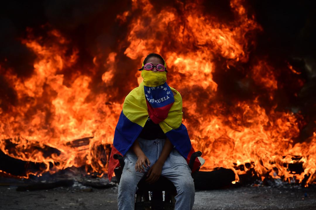 2017年4月24日,委內瑞拉一名反政府示威者坐在焚燒的路障前。