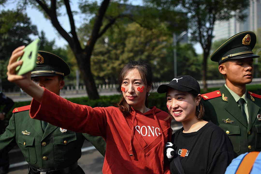 北京街頭,臉上貼著紅色貼紙的市民在解放軍身旁自拍合影。