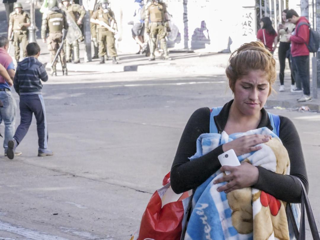 2019年10月25日,智利城市瓦爾帕萊索(Valparaiso)街頭,一名市民經過軍警。