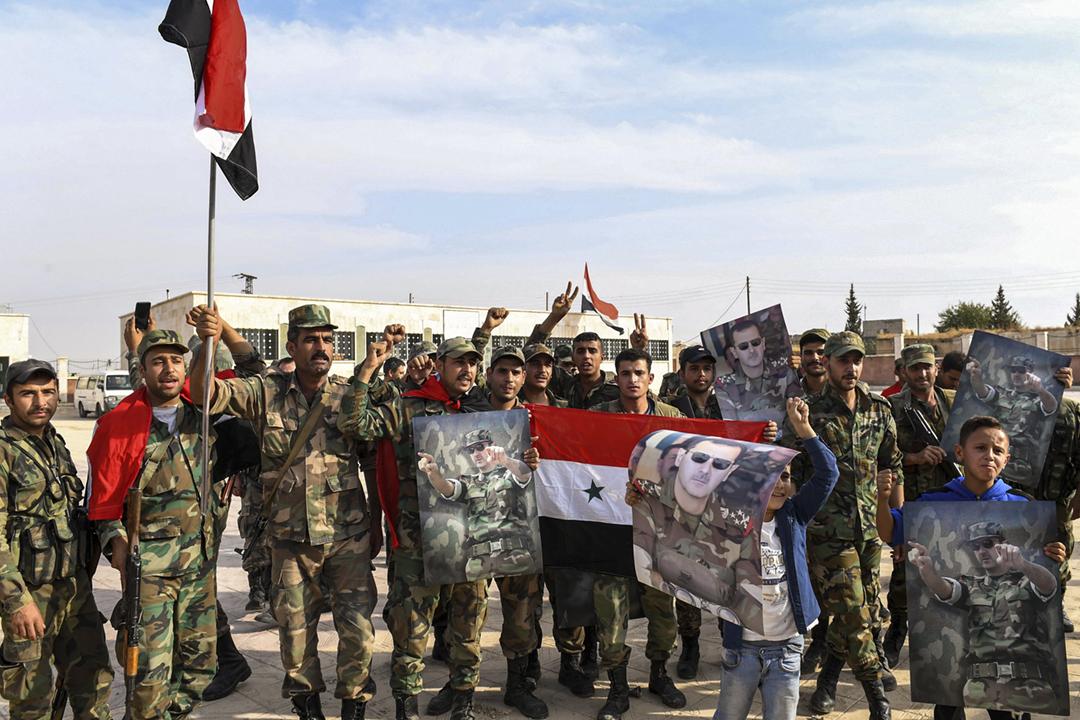 2019年10月15日,敘利亞政府軍在時隔七年後重新掌控北部重鎮曼比季(Manbij),有士兵手持國旗及總統巴沙爾・阿薩德(Bashar al-Assad )的肖像慶祝。 圖片來源:AFP via Getty Images