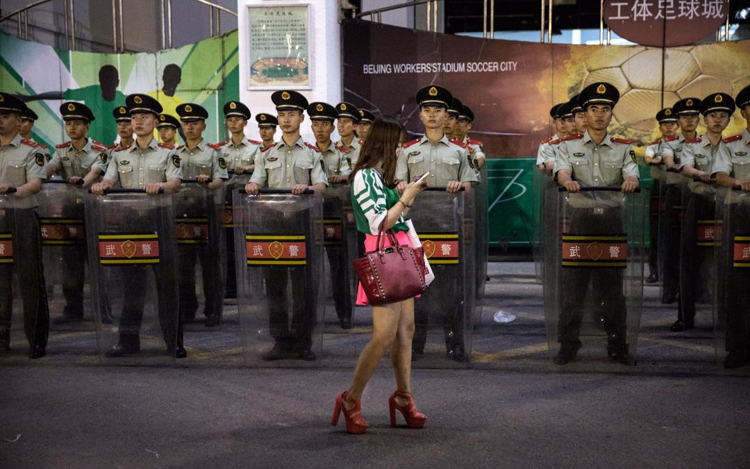 足球場外,一名使用智能電話的女子在武警面前經過。