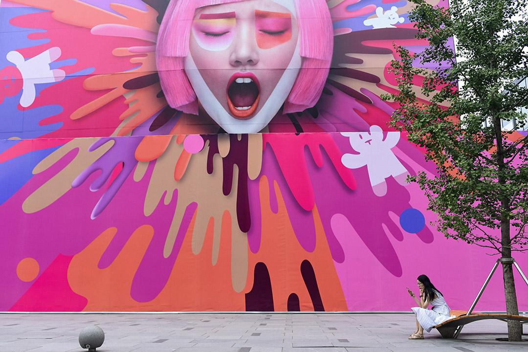北京一家商場外,婦女看著她的手機。