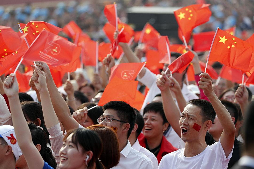 國慶閱兵儀式現場,觀眾揮舞著手中的紅旗。