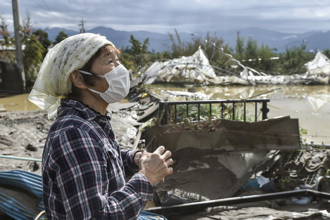 2019年10月14日,一名女士於長野縣長野市一間被颱風吹襲損壞樓房前。 攝:The Yomiuri Shimbun via AP Images