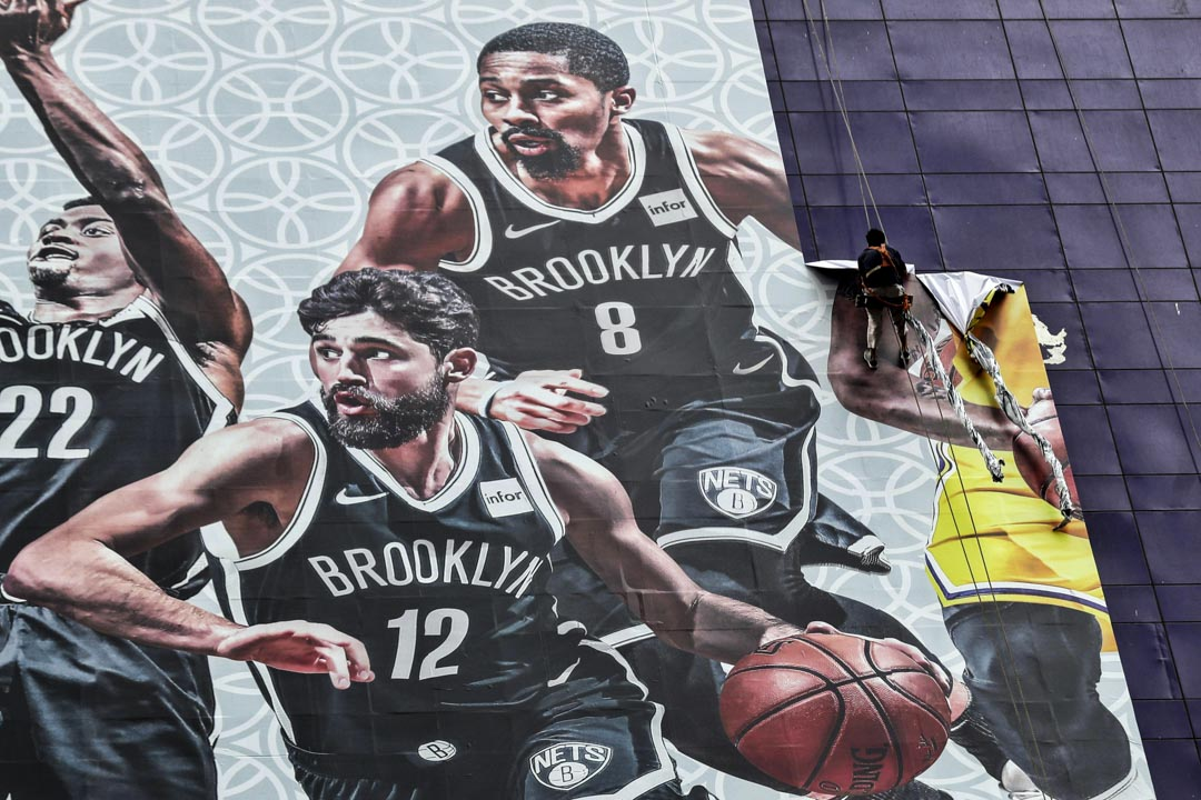 2019年10月9日,上海的陸家嘴正大廣場,在布魯克林籃網隊和洛杉磯湖人隊之間舉行的NBA上海比賽2019之前,一名工人於從建築物上拆除一張大海報。