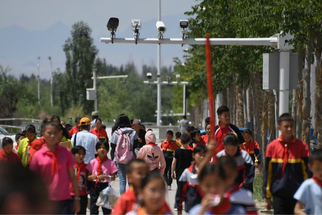 2019年6月4日,新疆喀什地區以南的阿克陶縣(Akto),一群學生在攝像頭下走過。 攝:Greg Baker/Getty Images