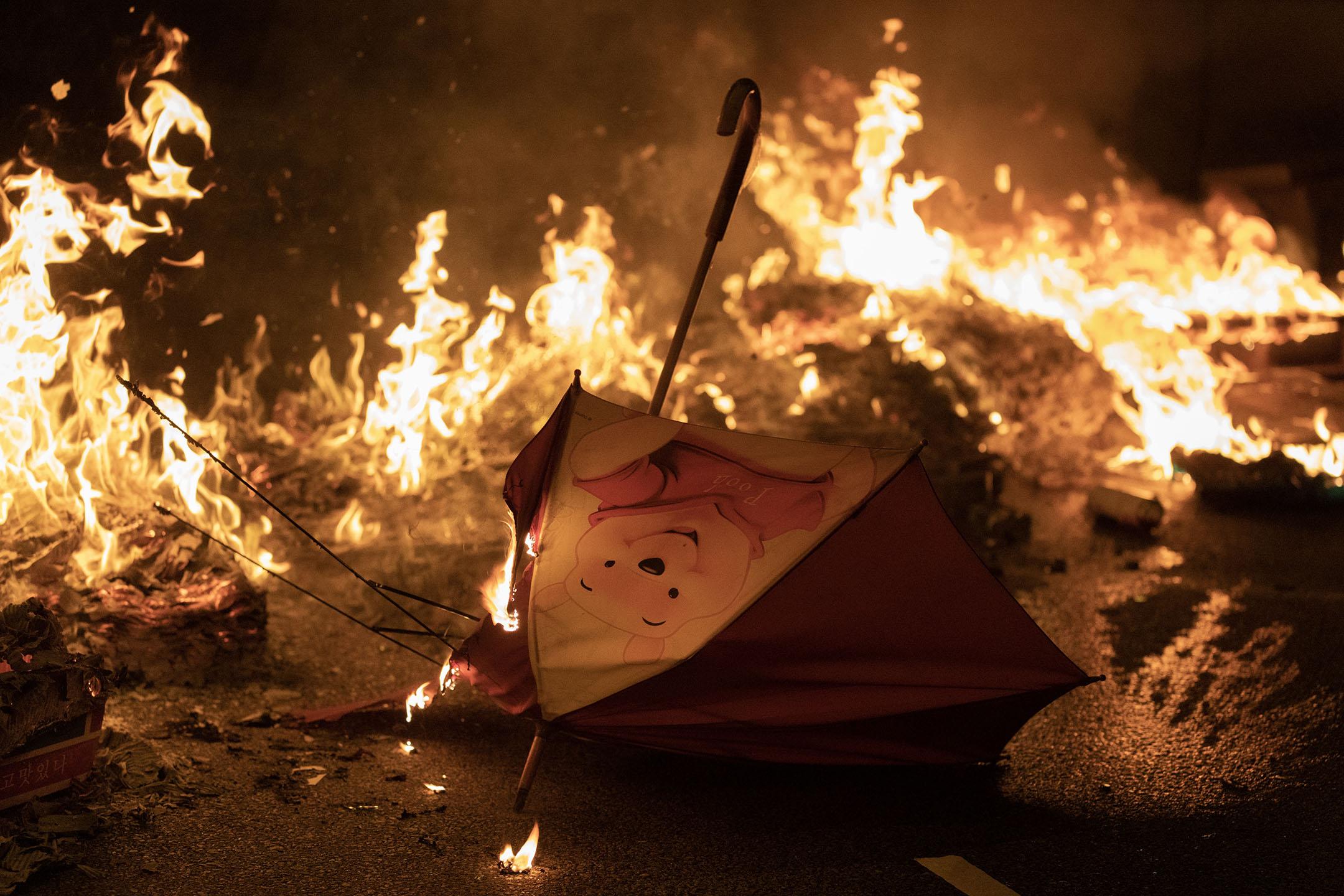傍晚7點左右,荃灣示威者在馬路設置路障、放火,圖為燃燒中的傘。 攝:廖雁雄 / 端傳媒