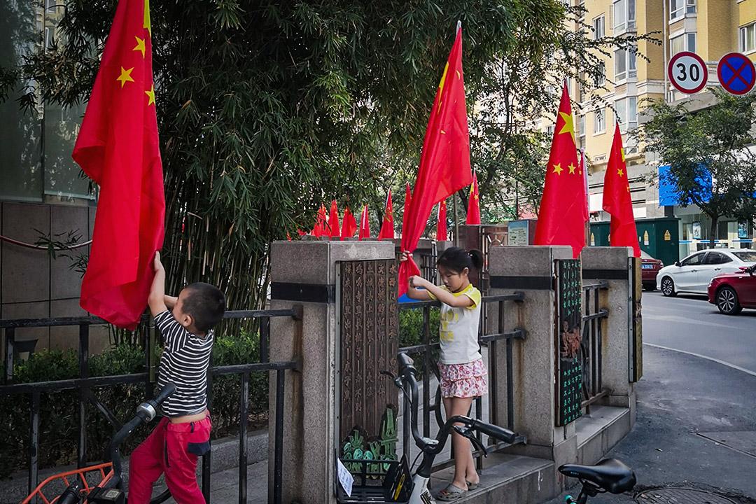 九月底的南京,兩個兒童在國旗欄杆旁一邊攀爬,一邊自顧自的玩耍。