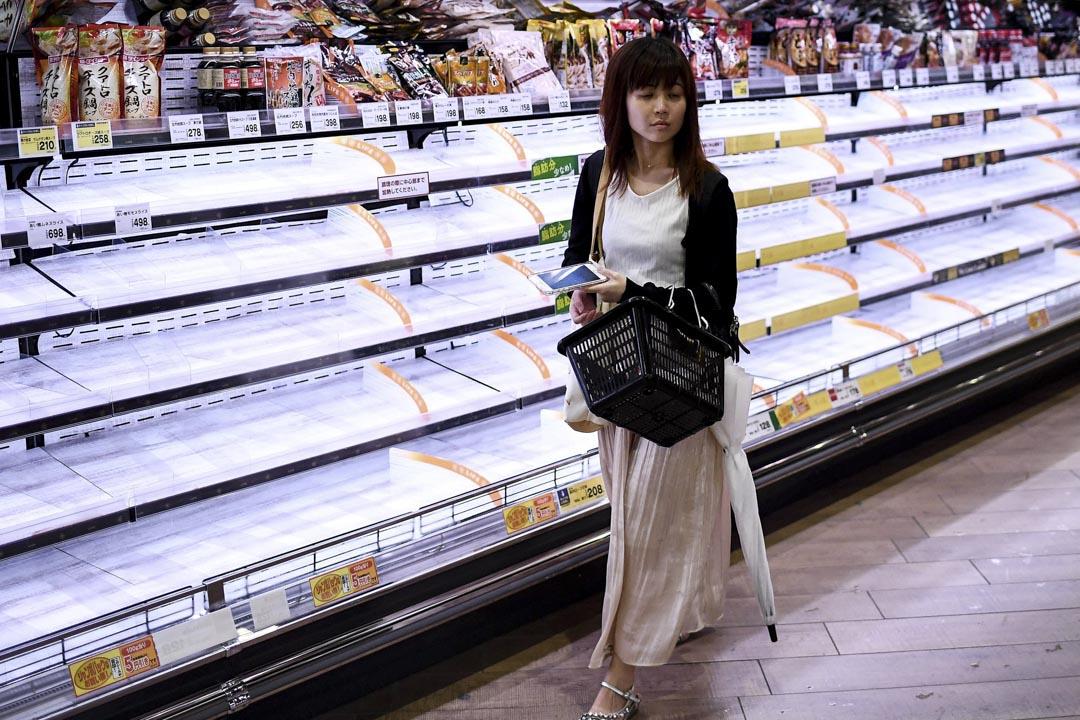 2019年10月11日,一位女士在東京一間超市,貨架上物品已被搶購一空。
