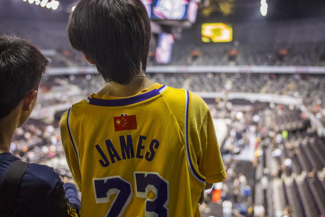 2019年10月12日,NBA中國賽深圳站湖人對籃網,有球迷穿上湖人球衣入場支持,其背後NBA標誌被中國國旗貼紙遮掩。 攝:林振東/端傳媒
