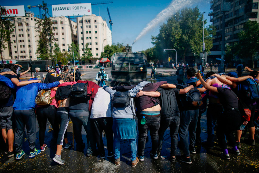 2019年10月20日,智利示威者在水炮車前築起人鏈。