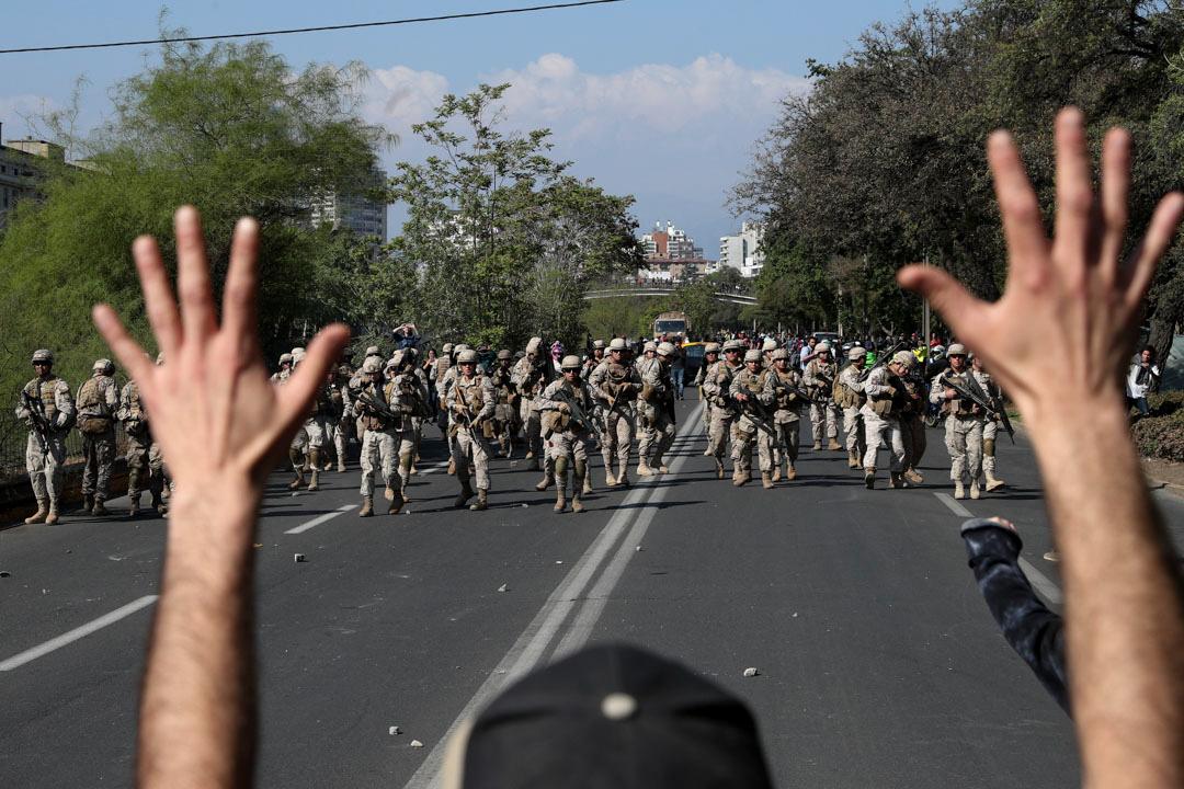 2019年10月20日,一名智利示威者在軍隊面前舉起雙手。