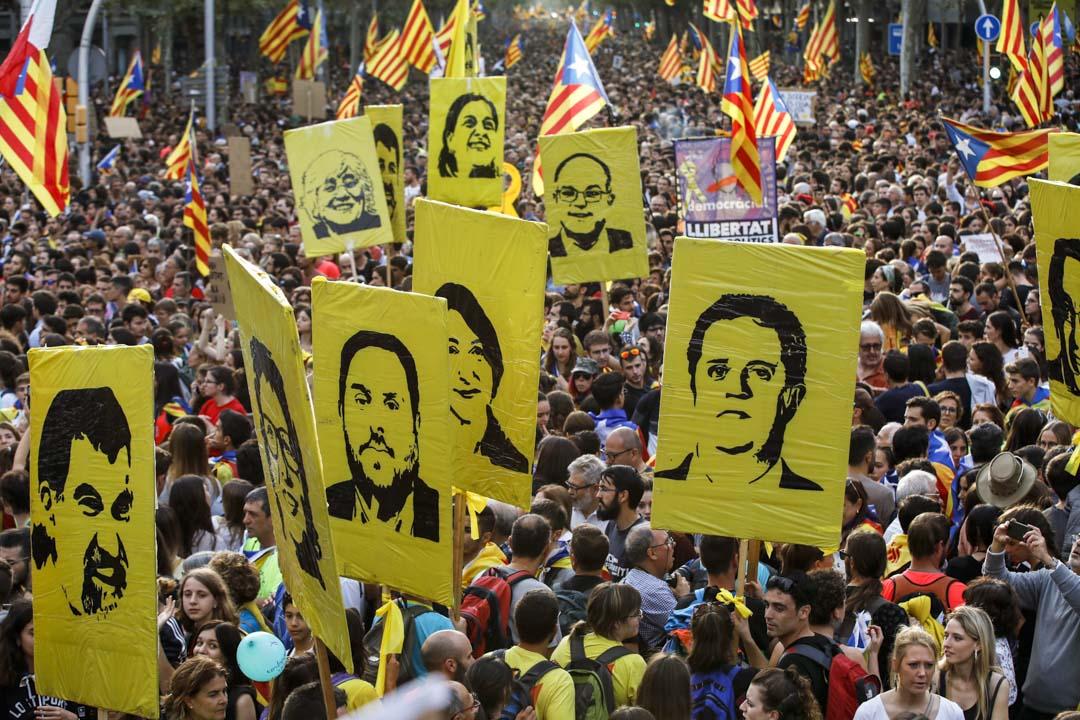 2019年10月18日,巴塞羅拿舉行的一場遊行中,參加者高舉加泰羅尼亞獨派領袖的畫像。