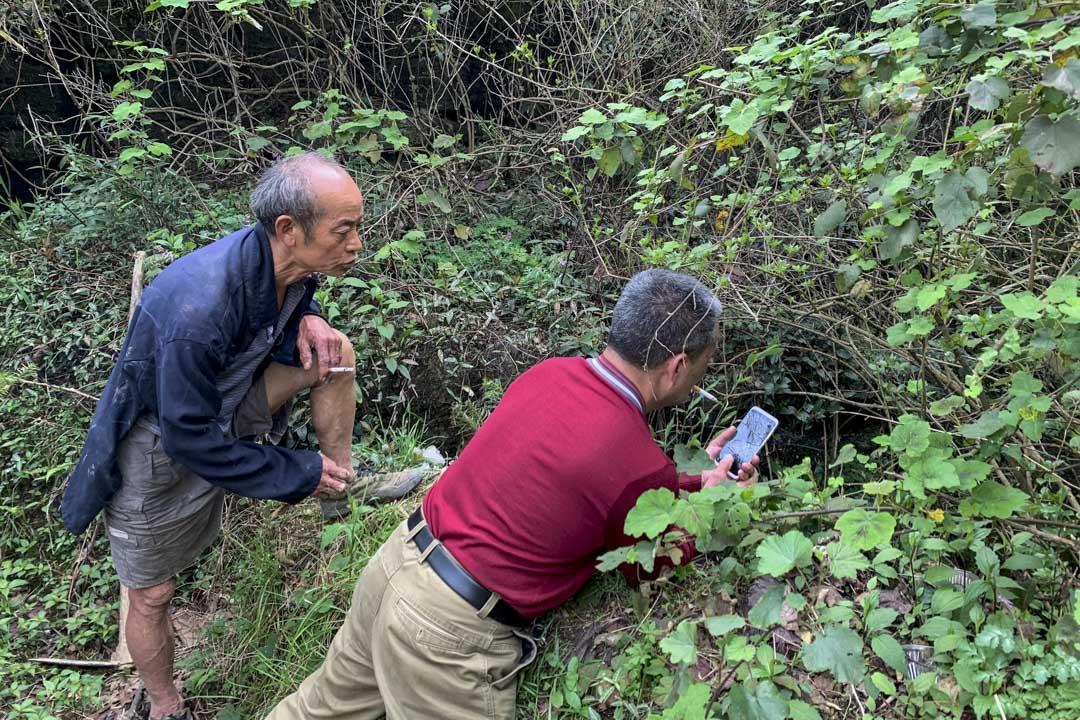 黃瓜冲村村民李太蘭和曾參與文革平反的幹部王德佳向天坑下探望。