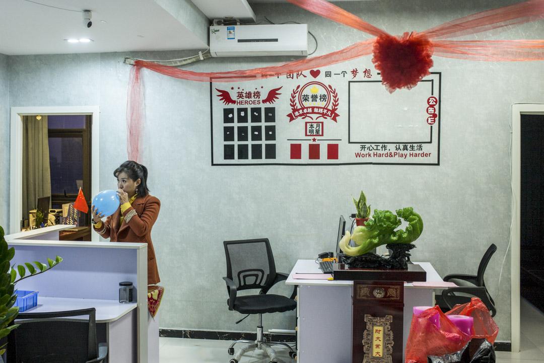 婚介公司的職員在婚禮當天的清晨,忙着佈置「娘家」及吹氣球。