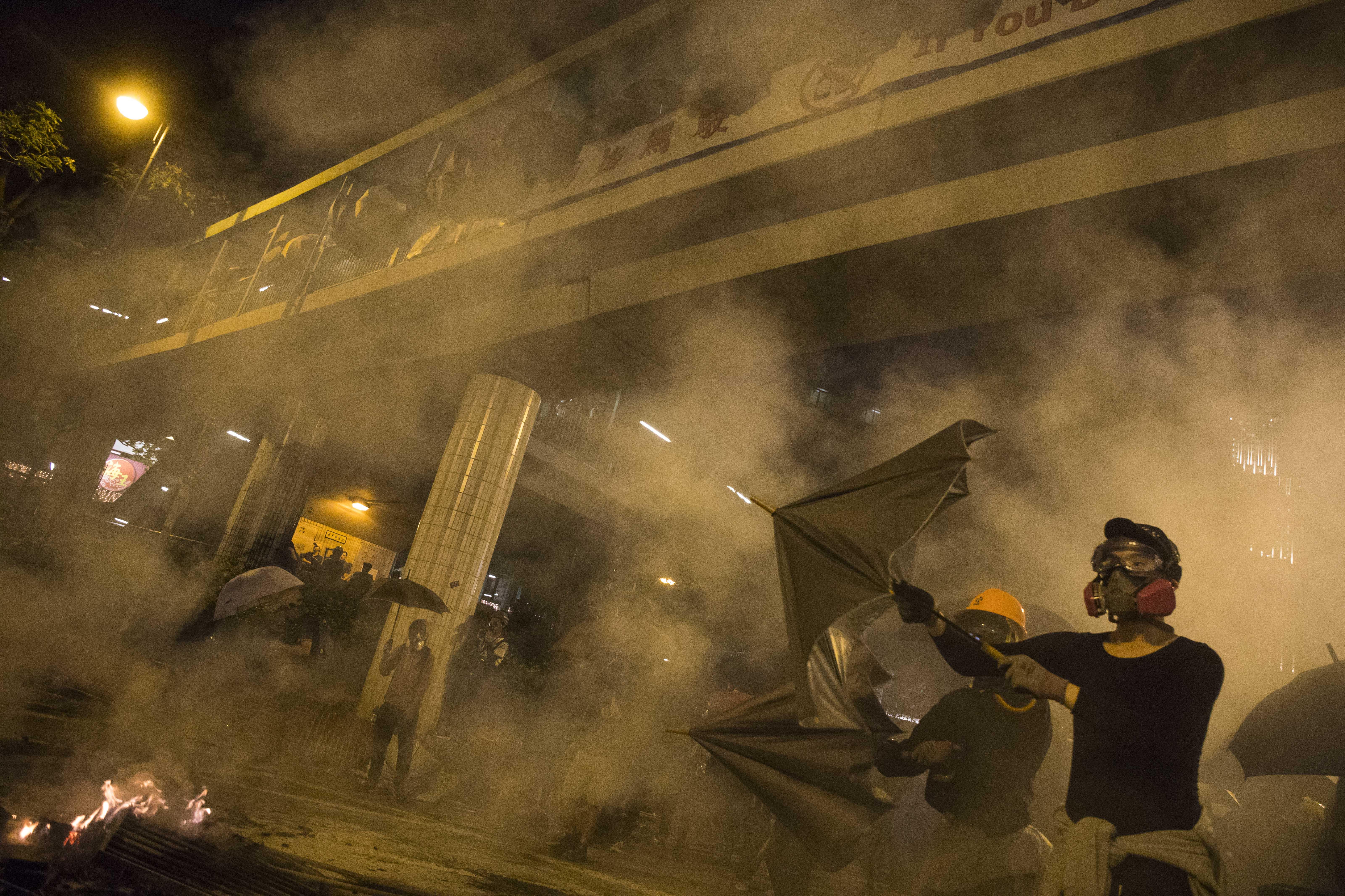 2019年11月18日,示威者在理工大學外身處警方施放的催淚煙霧中。