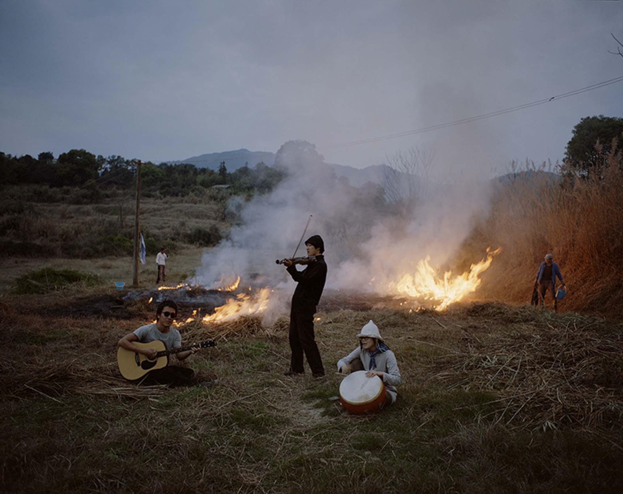 社區成員們在墾荒前將蘆葦和野草燒掉,吉富遙樹、唐冠華和邢振(左至右)見到燒荒的場景後,臨時起意趕到現場演奏。 攝影:李雋輝