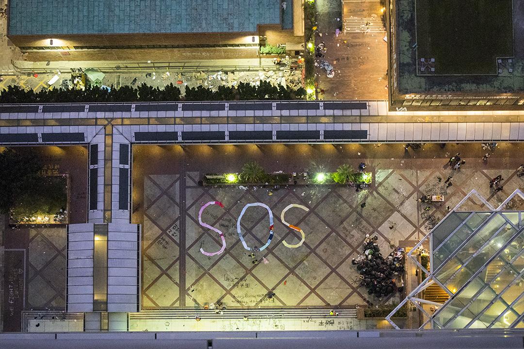 2019年11月19日傍晚時分,理大校園平台出現「SOS」(求救)的標誌。 攝:陳焯煇/端傳媒