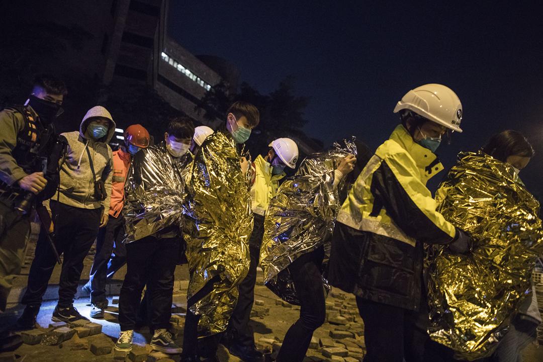 2019年11月20日,部份留守理工大學的示威者在醫護人員陪同下離開校園。 攝:陳焯煇 / 端傳媒