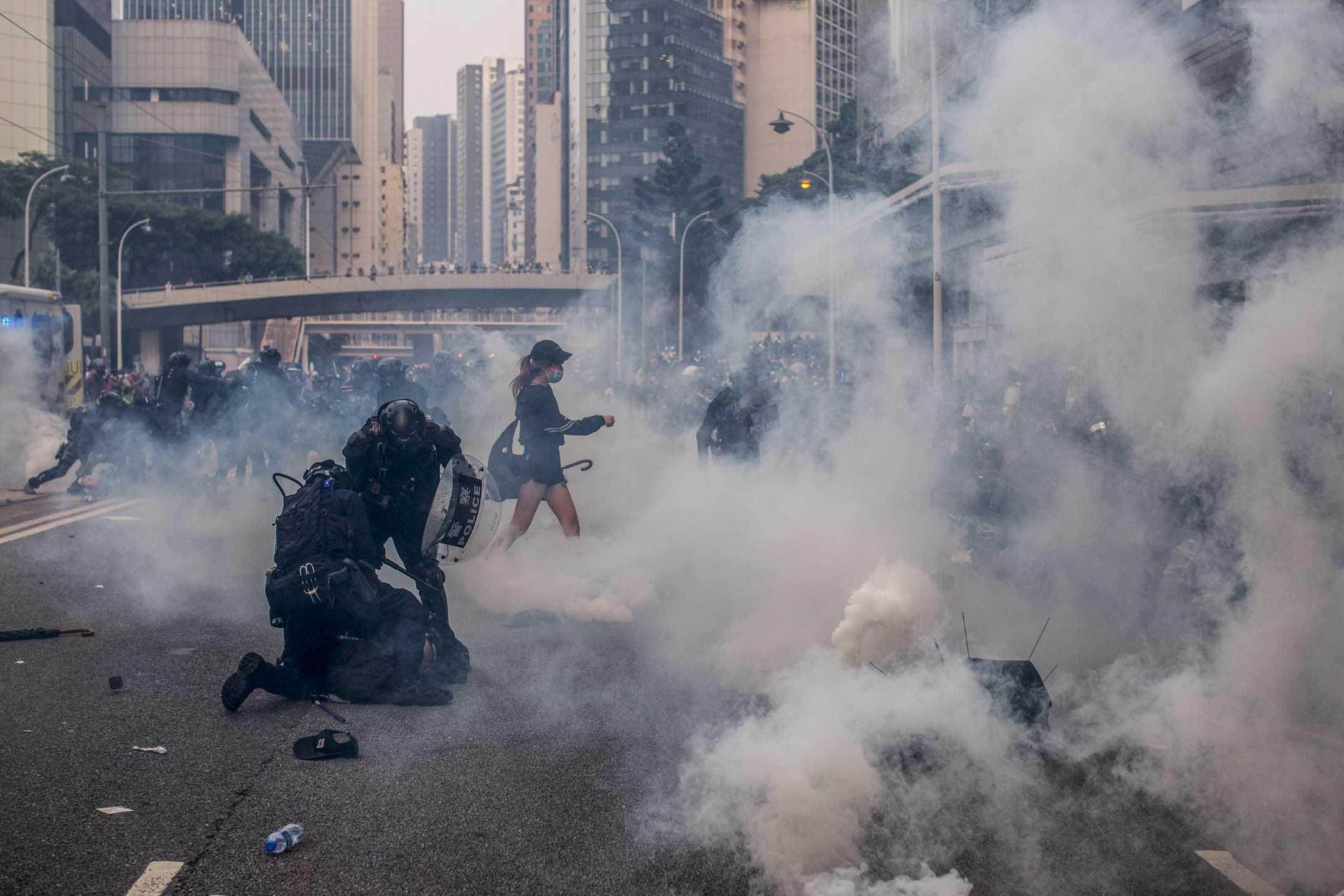 2019年9月29日,大批防暴警察到金鐘拘捕示威者,一名女士走過現場。