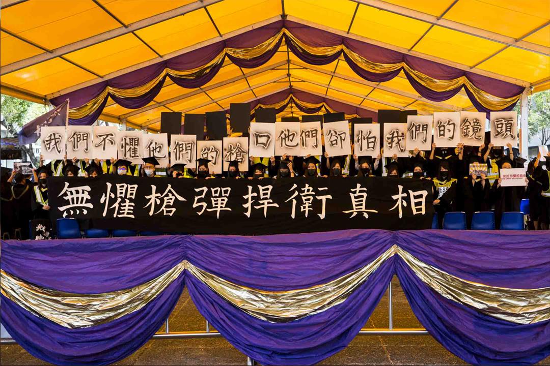 2019年11月7日香港中文大學舉行畢業典禮,有新聞與傳播學系畢業生在台上舉起標語,抗議警方近月粗暴阻撓傳媒採訪示威。 攝:林振東 / 端傳媒