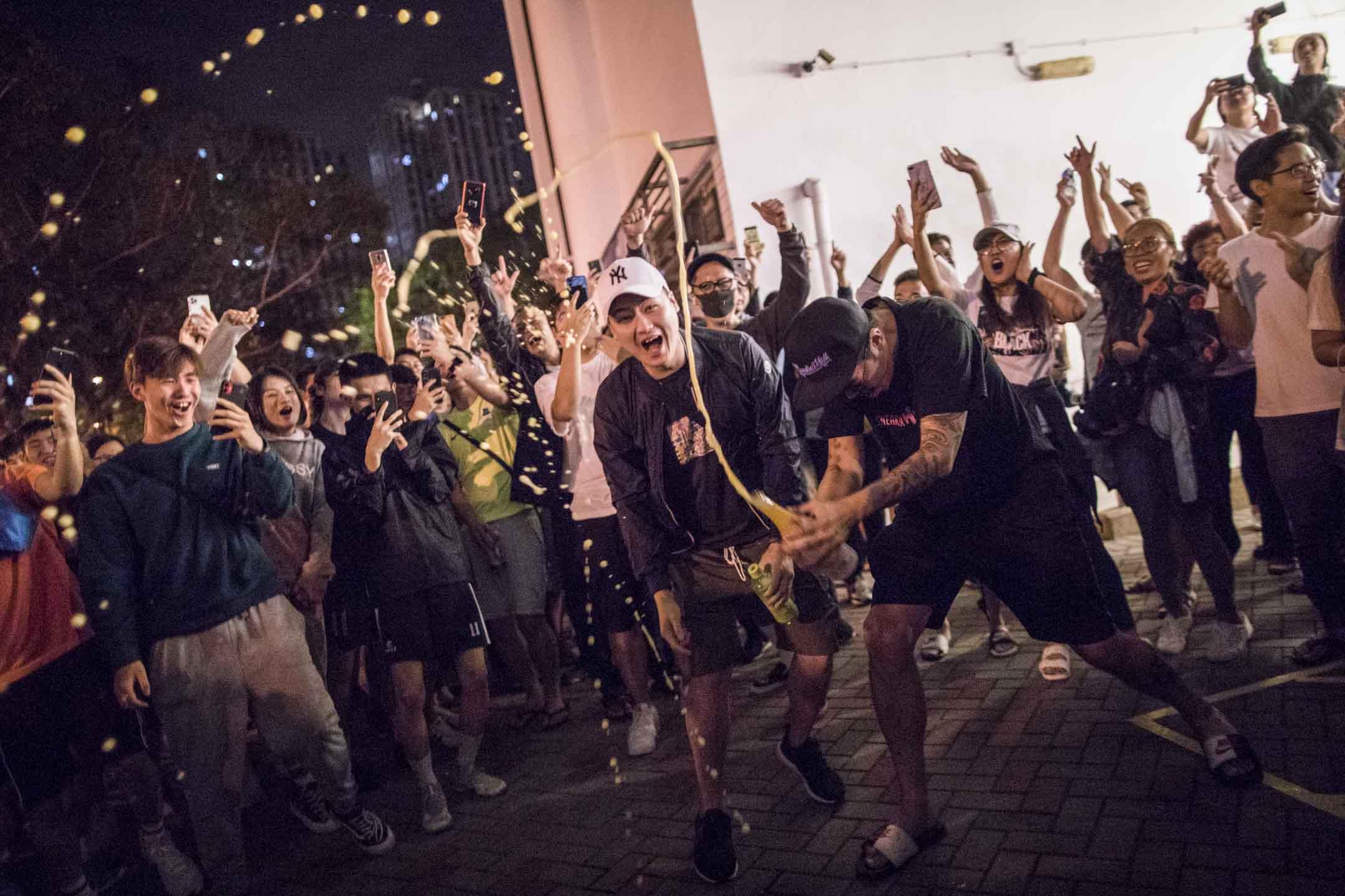 2019年11月25日凌晨,屯門樂翠選區區議會點票結果出爐,何君堯落敗,站外大批市民開香檳慶祝。 攝:陳焯煇/端傳媒