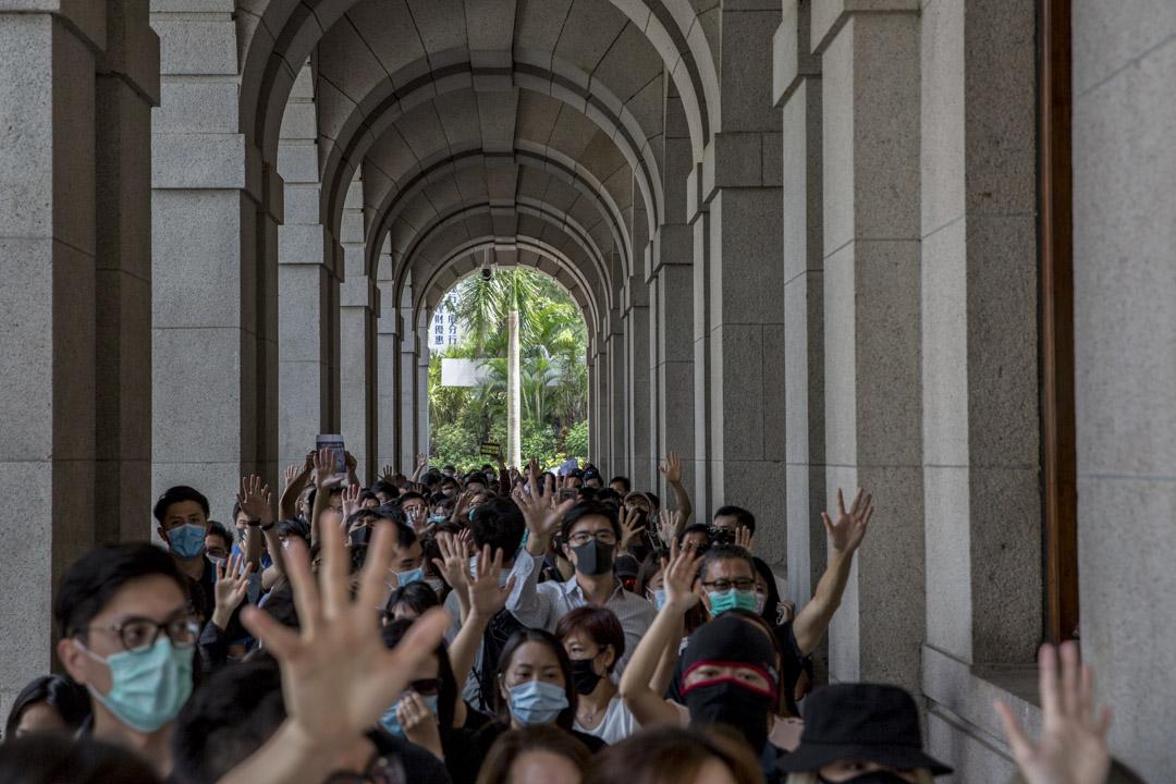 2019年10月4日,香港中環上班族戴口罩、伸出五指,要求政府回應「五大訴求」。 攝:林振東/端傳媒