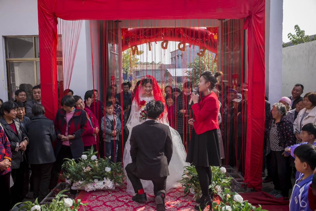 小彬在婚禮的舞台上,向新娘家鄉跪地獻花。