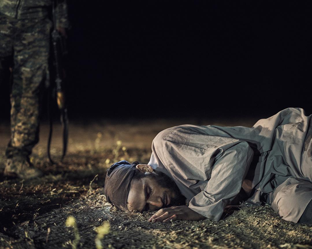 """一名走出巴古茲包圍圈投降的外籍""""伊斯蘭國""""傷兵側卧在艾什沙法赫丘陵附近的臨時甄別處。"""