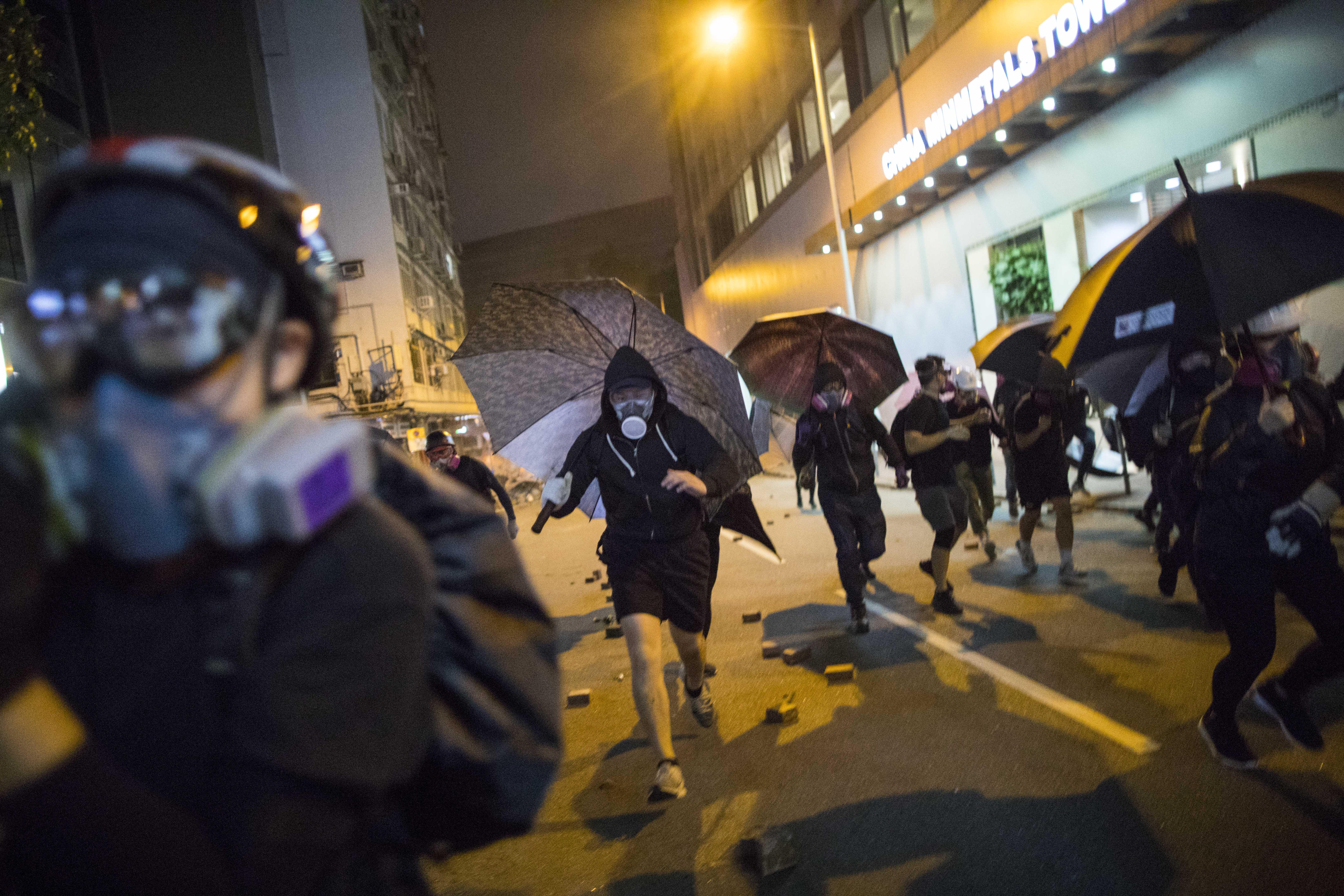2019年11月18日,理工大學外,有示威者撐著傘奔跑。