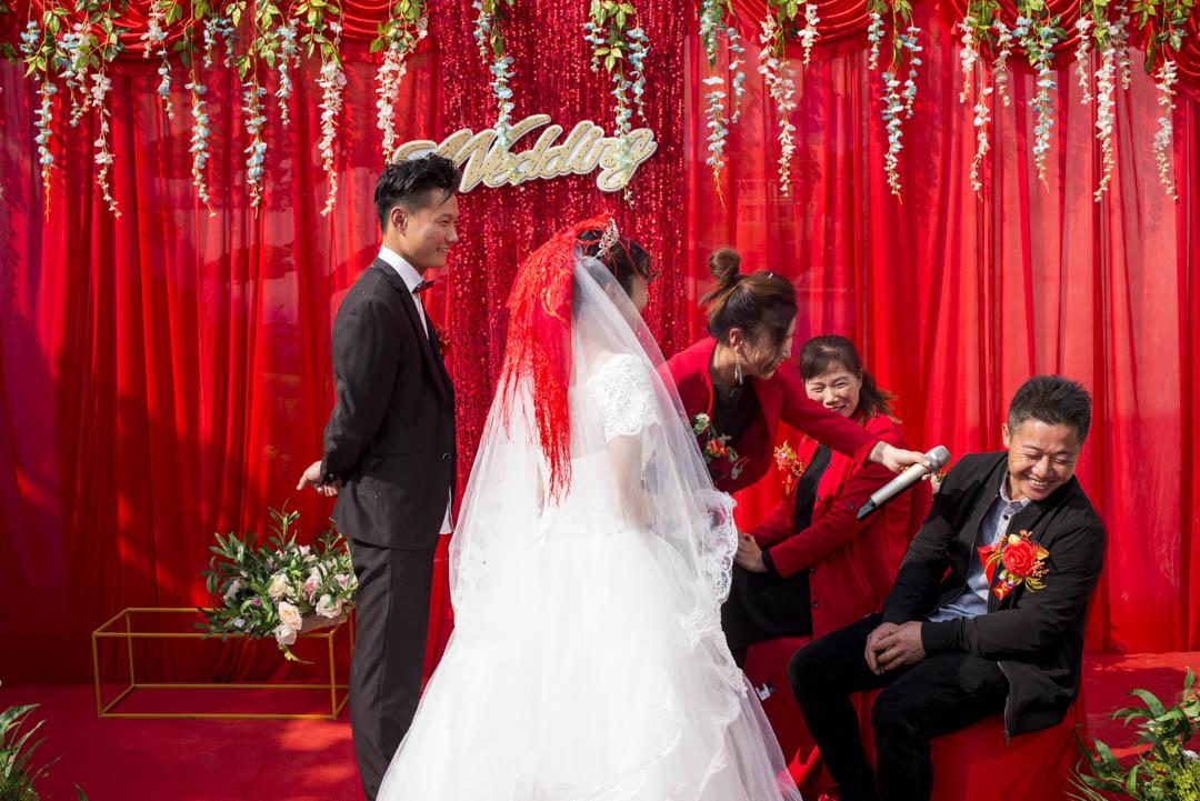 新人拜父母,小彬的父母坐在舞台上,顯得很害羞。