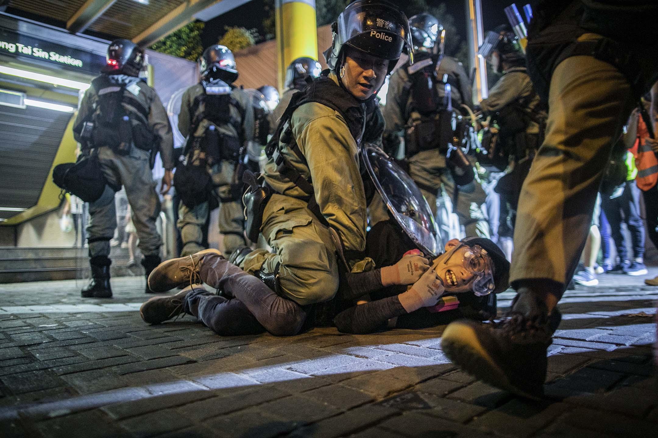 2019年8月24日,一名警員在黃大仙制服一名示威者。 攝:陳焯煇/端傳媒