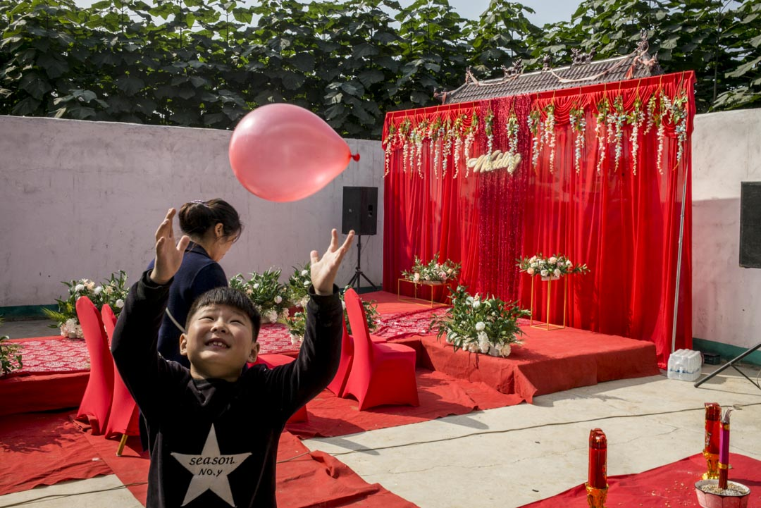 院子裏有一座紅色舞台,是李總團隊當天凌晨搭好的。一條紅毯T台,圍繞着仿真的白色玫瑰,象徵愛情的純潔。