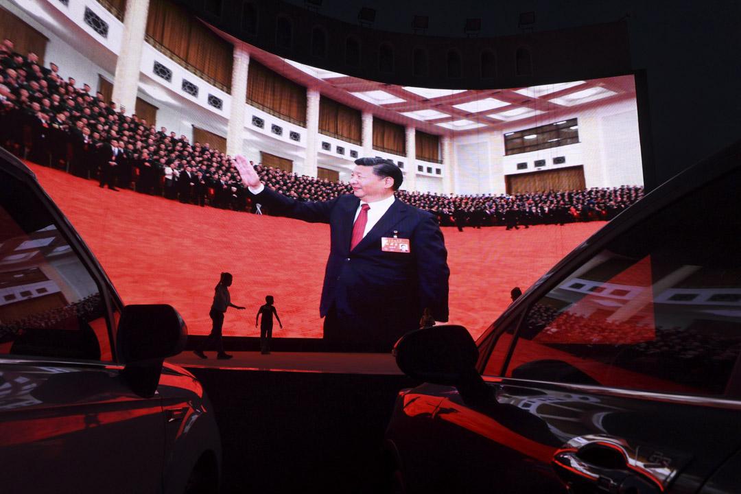 2019年6月1日,中國西部新疆地區喀什一幅屏幕上播放國家主席習近平片段,孩子們在屏幕旁玩耍。